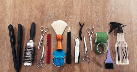 Hairdressing accessories arranged on wooden background