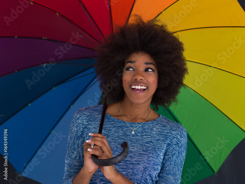 african american woman holding a colorful umbrella - 164349396