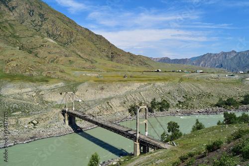 Suspension bridge across Katun river near village in Altai mountains. Inya, Altay Region, Siberia, Russia.