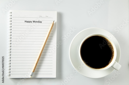 Poster White cup of coffee morning on wooden table with notebook