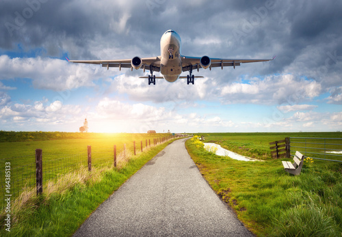 Airplane and rural road. Landscape with passenger airplane is flying over the asphalt road against cloudy sky, green grass field. Journey. Passenger aircraft is landing on the runway. Commercial plane