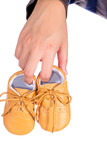 Children's shoes on women's hand on wooden background.