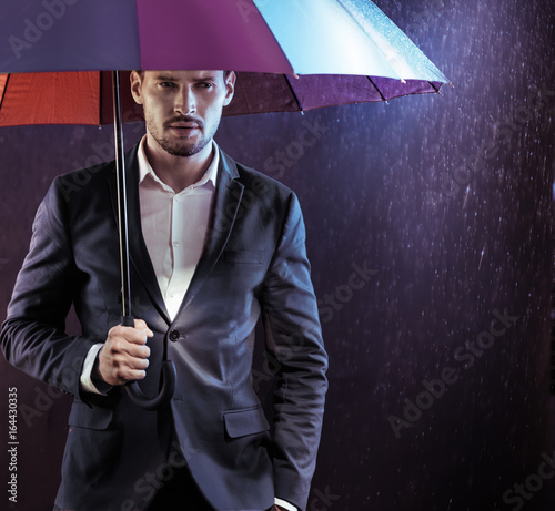 Portrait of a calm, serious businessman holding a colorful umbrella