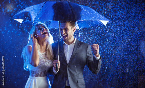 Cheerful couple enjoying the summer rain