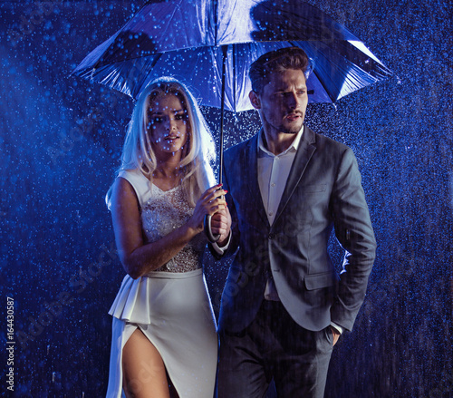 Fashion style portrait of a couple posing in the rainy weather