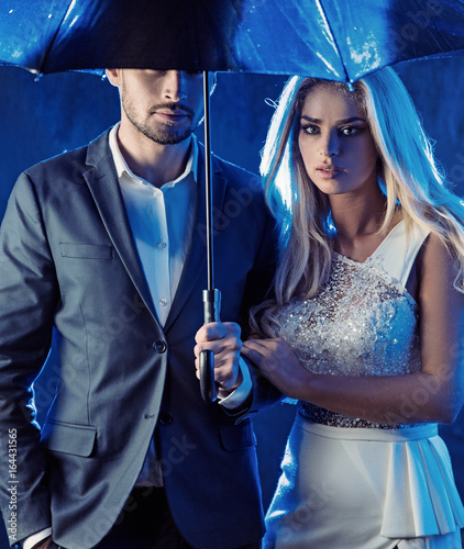 Amorous couple posing on a rainy bacground