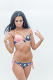 Young beautiful black-haired woman posing on the beach