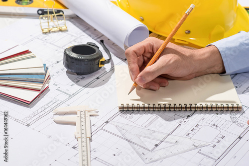 Working on blueprints. Construction project with hands writing on notebook.