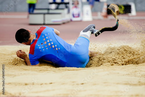 long jump athlete paralympic disabled landing in sand Poster
