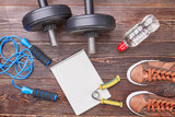 Sport equipment background. Jumping rope, dumbbells, bottle, sneakers, expander, notebook, wooden background.