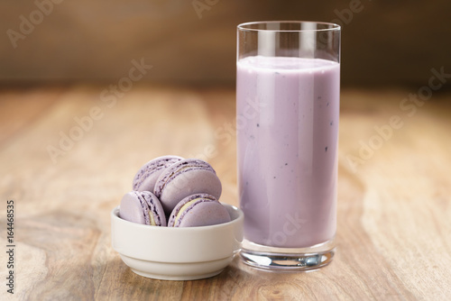 violet macarons in white bowl with blueberry yogurt on wooden table
