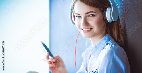 Plakát Smiling girl with headphones sitting on the floor near wall