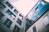 Sonne und Wolken spiegeln sich in Glasfassade eines Geschäftsgebäudes - 164471321