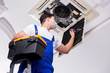 Worker repairing ceiling air conditioning unit - 164483505