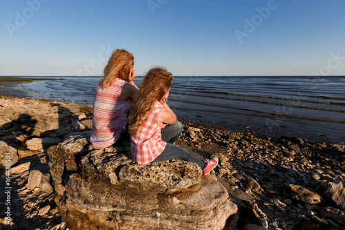 Little girl and her mother sitting on a rocky shore and looking at the sea.