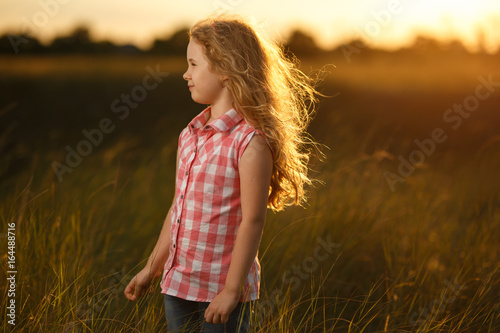 Little blonde child girl standing in summer field at sunset.