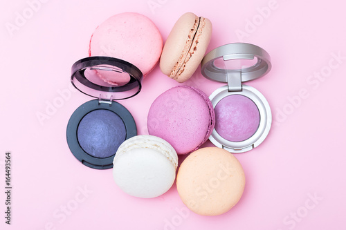 Sweet macaroons and eye shadow round on a pink background