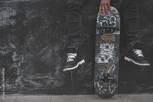 Fotobehang Skateboard Legs in sneakers at the skateboard