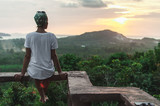 The view from the back of a woman sitting on a high and watching sunset - 164500595