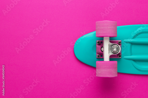 Fotobehang Skateboard plastic mini cruiser board on deep pink with background with copy space