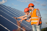 Worker and foreman maintaining solar energy panel. Technicians checking equipment for solar energy station. - 164506192