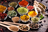 Variety of spices and herbs on kitchen table - 164507153