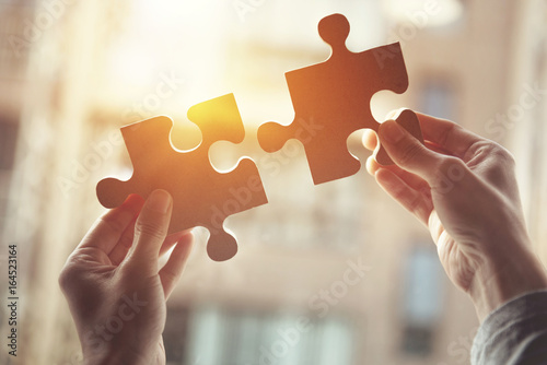 Businesswoman hand connecting jigsaw puzzle with sunlight effect, Business solutions, success and strategy concept. - 164523164
