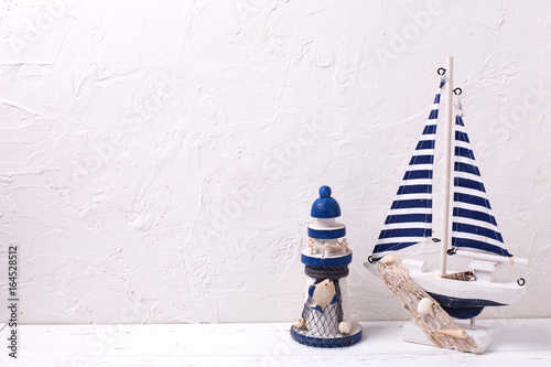 Decorative  wooden toys boat and lighthouse  on textured  white background.