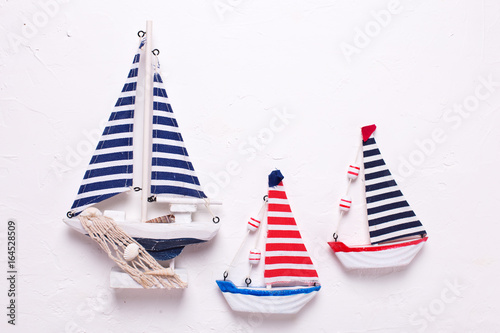 Three  decorative  wooden toys boats on textured  white background