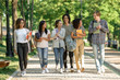 Happy young students walking outdoors