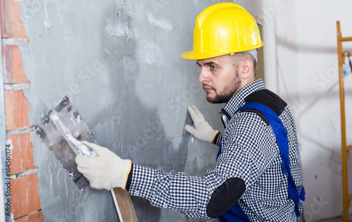 Smiling craftsperson in the helmet is plastering the wall © JackF