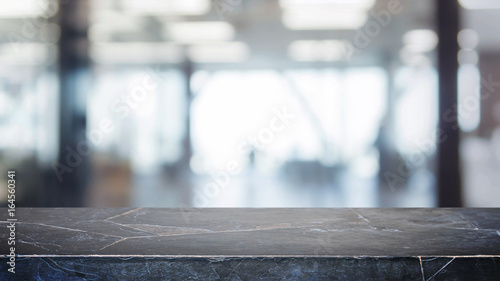Black stone table top and blurred bokeh office interior space background - can used for display or montage your products. - 164560341