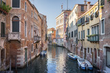 Canal with boats and historical buildings in Venice, Italy.