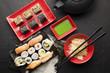 Sushi set and black teapot on black table - 164570545