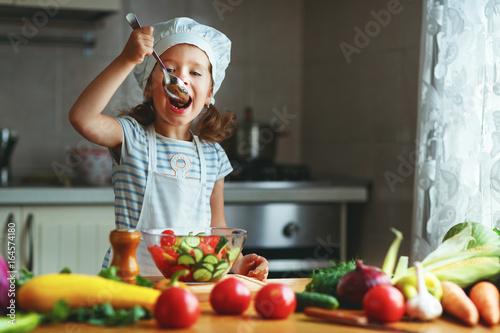 Healthy eating. Happy child girl prepares  vegetable salad in kitchen - 164574180