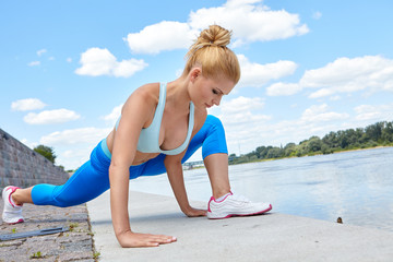 Sport woman making stretching before running in  city
