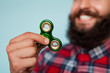 Young hipster man holding a fidget spinner toy