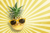 Fototapety Pineapple wearing sunglasses on sunbeam vintage background with copy space and pastel tone. In summer holiday.