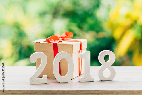 Poster New Year concept for 2018 : Wood numbers 2018 on wood table top and gift box with green light bokeh blur background