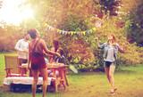 happy friends playing badminton at summer garden