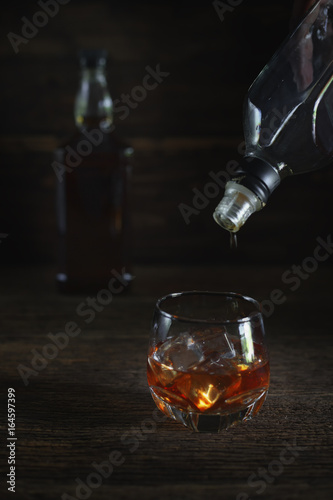 Glass of liquor on wooden floor in low light.