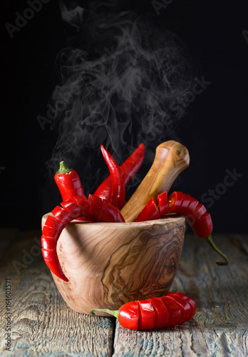 Red chili pepper in wooden mortar .