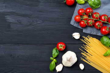 Food ingredients for spaghetti pasta with cherry tomatoes, basil leaves and garlic, black wooden background, top view with copy space
