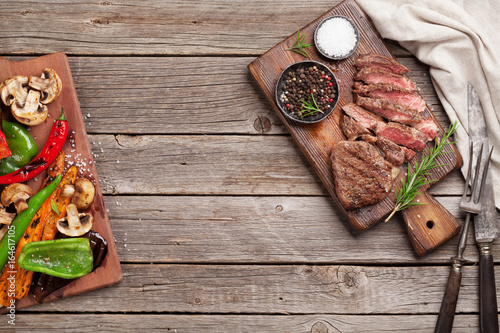 Beef steak and grilled vegetables on cutting board - 164617105