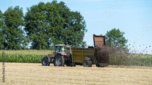 Fotobehang Trekker tracteur agricole qui épand le fumier sur le champ