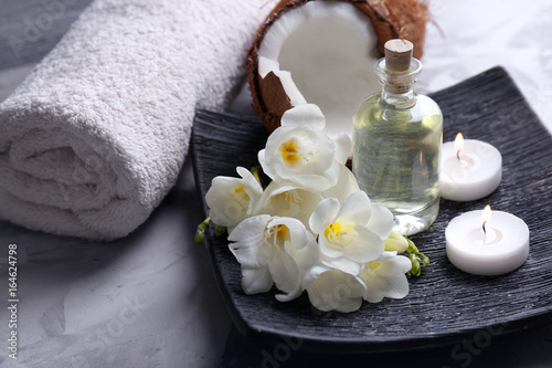 Composition with coconut oil in bottle for spa treatment on dark plate © Africa Studio