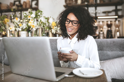 Young African American girl in glasses sitting in restaurant with laptop and cup of coffee in hands. Smiling girl with dark curly hair looking in laptop. Portrait of lady in white shirt with earphones