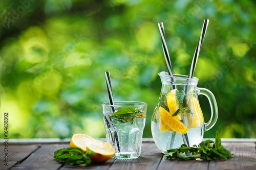 Lemonade in the jug and lemons with mint on the dark rustic wooden table outdoor