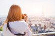tourist photographer in Paris taking photo of Eiffel tower and panoramic view of the city
