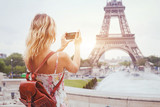 tourist in Paris visiting landmark Eiffel tower, sightseeing in France, woman taking photo on mobile phone